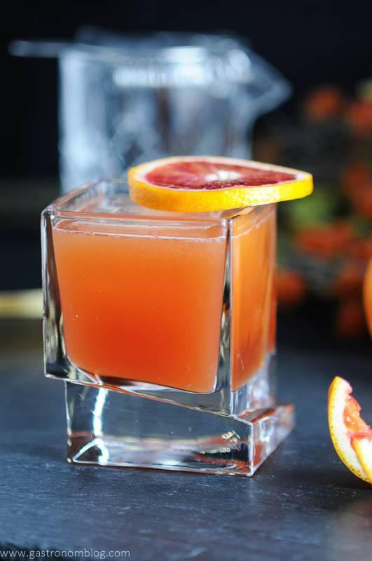 The Blood and Bourbon Cocktail, made with fresh squeezed Blood Orange Juice, Bourbon, Simple syrup and a dash of lemon. Garnished with a slice of blood orange. Finished with aromatic bitters. Rocks Glass by Joy Jolt.