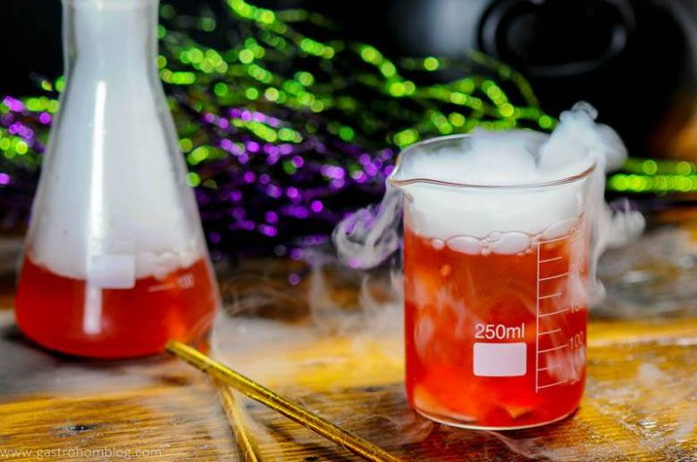 Red Halloween Cocktail in laboratory beakers. Gold straws and silver cocktail shaker. Dry ice over all.