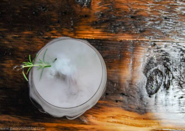Top shot of a dry ice cocktail with rosemary sprig.