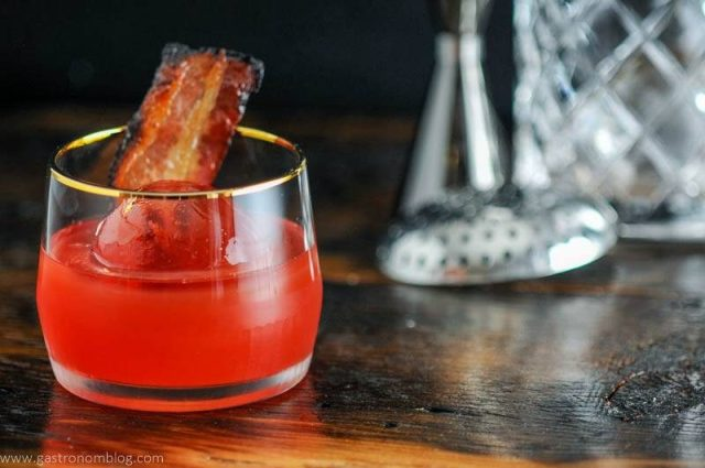 Cocktail in gold rimmed rocks glass with bacon