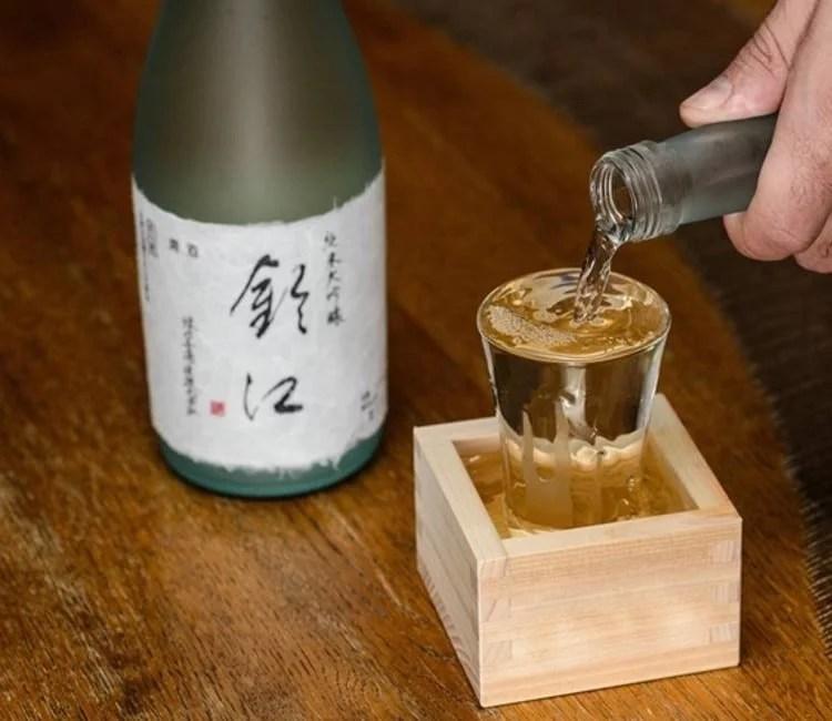 Service du saké débordant dans sa boîte Masu en bois
