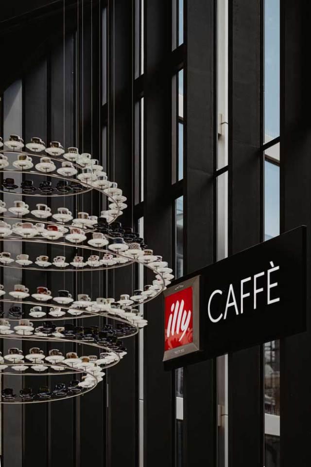illy Caffè Innsbruck Der spektakuläre Kronleuchter, direkt an der Decke des Kaufhauses Tyrol, besteht aus ungefähr 100 illy Art Collection Tassen. Er symbolisiert eine Reise durch die Sammlungen berühmter zeitgenössischer Künstler und junger aufstrebender Künstler seit 1992.