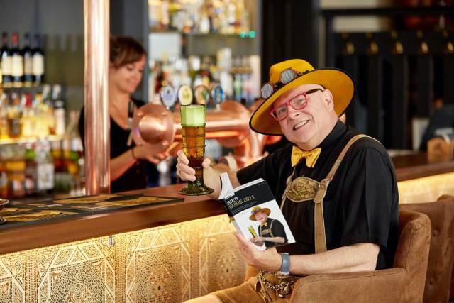 """Bier Guide 2021 Auf dem Cover des Guides posiert Conrad Seidl mit einem nach historischem Vorbild hergestellten Glas: Es handelt sich um ein mundgeblasenes Passglas, wie es in früheren Jahrhunderten zu Trinkspielen verwendet worden ist. Es geht um das """"Passtrinken"""", bei dem man von einem Ring zum nächsten trinken musste."""