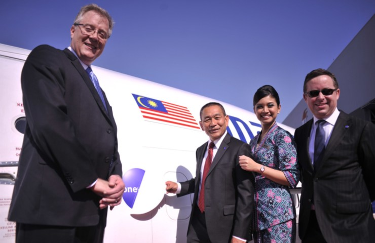 Malaysia Airlines' cabin crew with Malaysia Airlines Group CEO Ahmad Jauhari Yahya (second from left) and Malaysia Airlines Chairman Tan Sri Md Nor Yusof (second from right) giving the thumbs up. In the background is Malaysia Airlines' B737-800 with the oneworld livery.