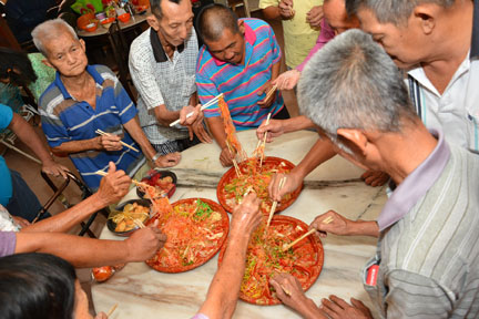 Prosperous toss: Elderly tossed yee sang with resort staff to ring in good fortune and auspicious year of the Horse.
