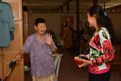 Auspicious moment: Connie Chin, Director of Marketing Communications spending time with one of the residents with Chinese New Year cookies.