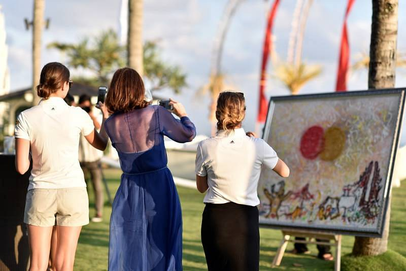 The MasterCard team taking photos of the MasterCard inspired artwork by a local Balinese fire painter during the Priceless Bali launch