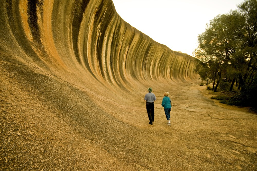 Couple viewing the unique Wave Rock, located near Hyden. (Picture credit: Tourism Western Australia)