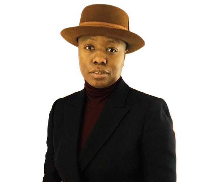 Photo of Black queer person with a brown hat, black jacket and burgundy turtle neck