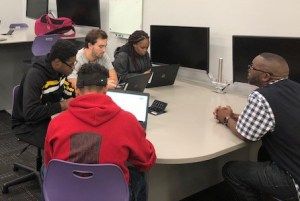 Students working with a counselor to complete forms