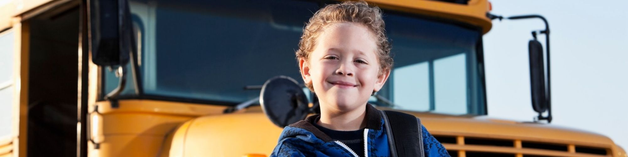 Child posed in front of bus