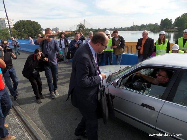 Prezydent Paweł Adamowicz obdarowuje pierwszego przejeżdżającego kierowcę