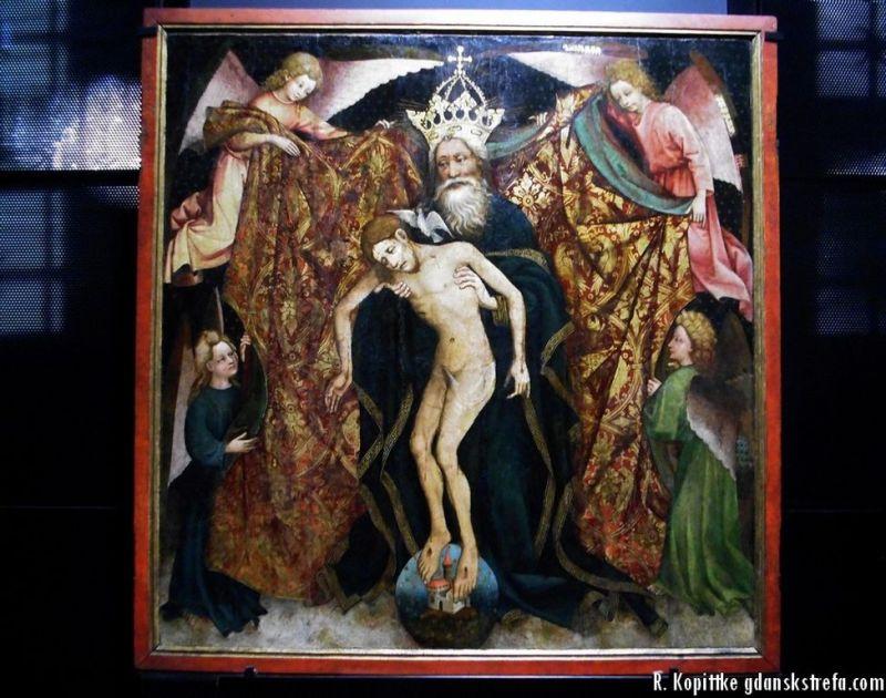 Bóg Ojciec prezentuje zdjęte z krzyża ciało Chrystusa, na znak pojednania z ludzkością. Oznaką odkupionego świata jest kulista sfera pod stopami Chrystusa. Pierwotna kolorystyka zmieniona na skutek rozległych przetarć warstwy malarskiej.