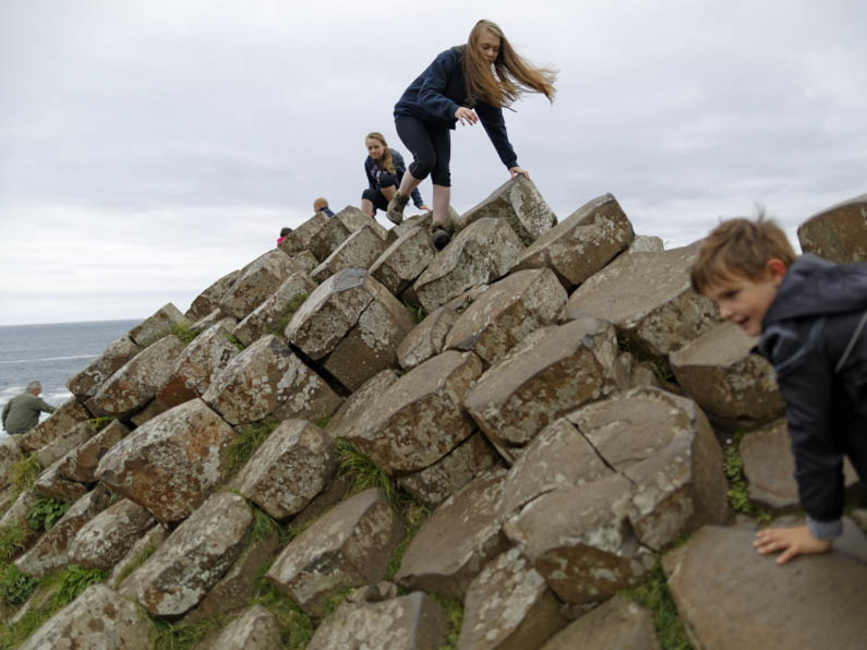 National Trust Properties Children clambering on the rocks at Giant s Causeway