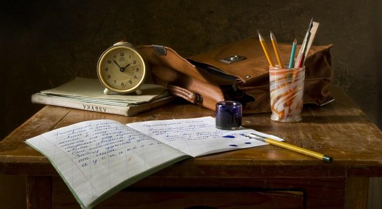 Schullbank mit einem Heft, Stiften, einem Wecker und einer Schultasche