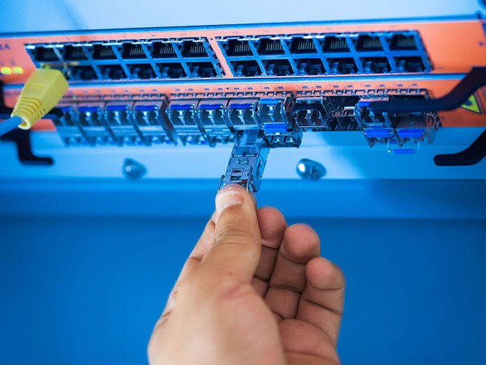 A human hand holding an Ethernet plug that is not inserted in the network switch