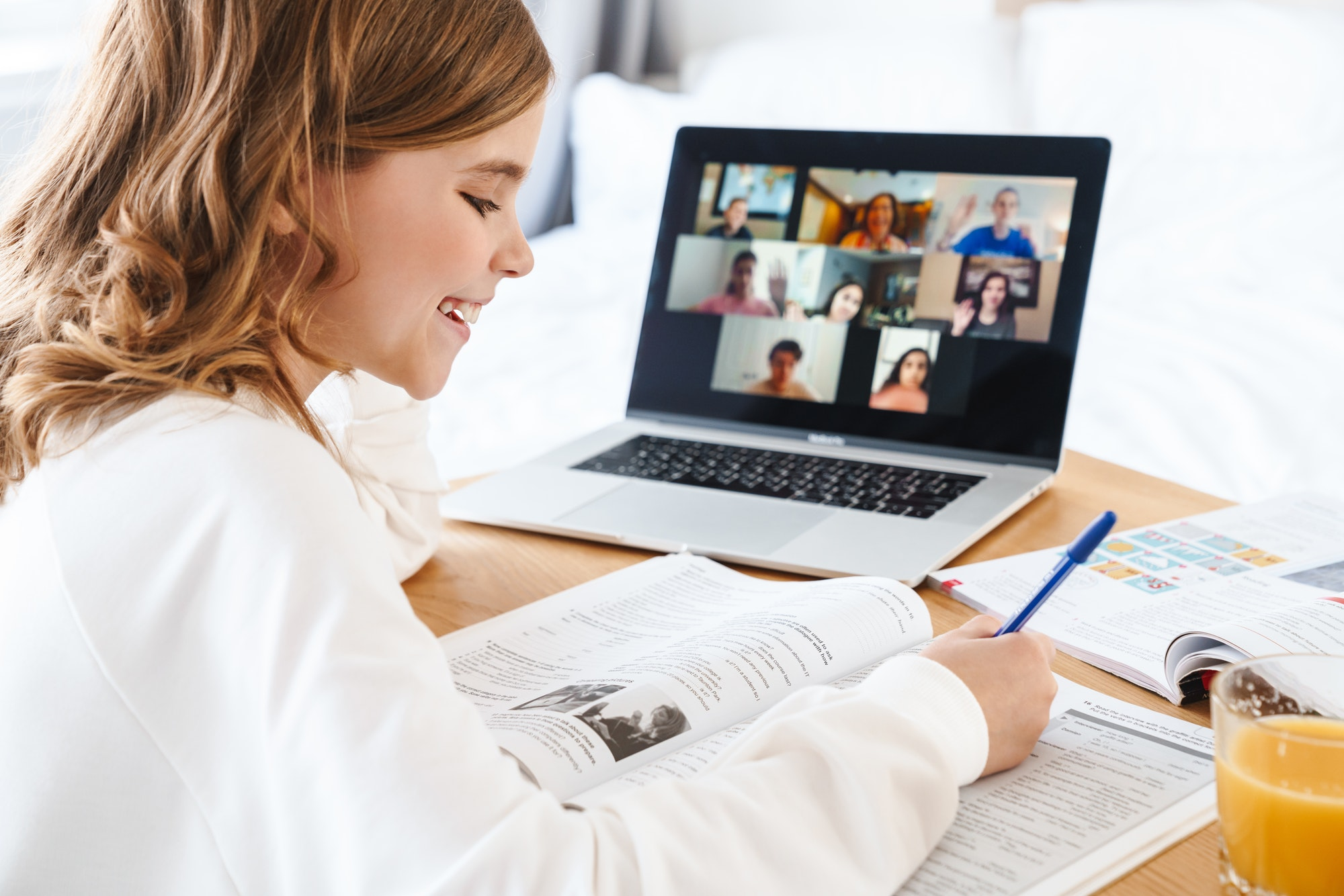Photo of girl writing in exercise book while studying online