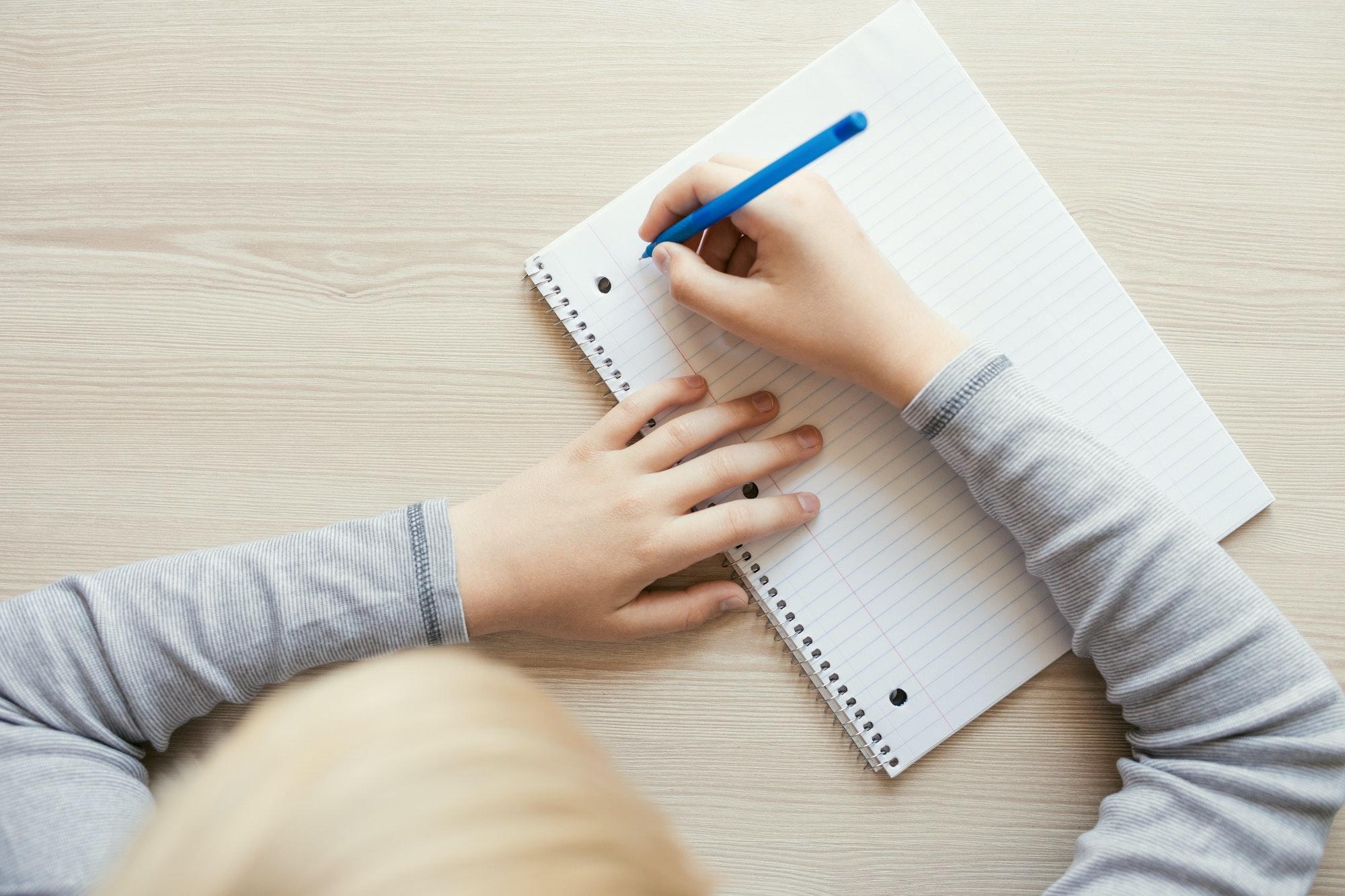 Kid Writing in Notebook.