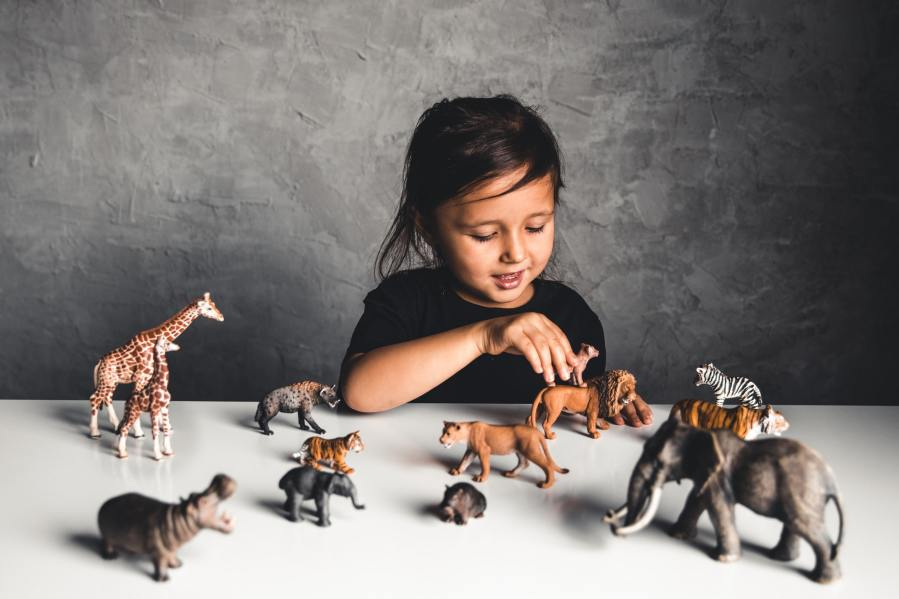 Little girl playing with animal toys in playroom