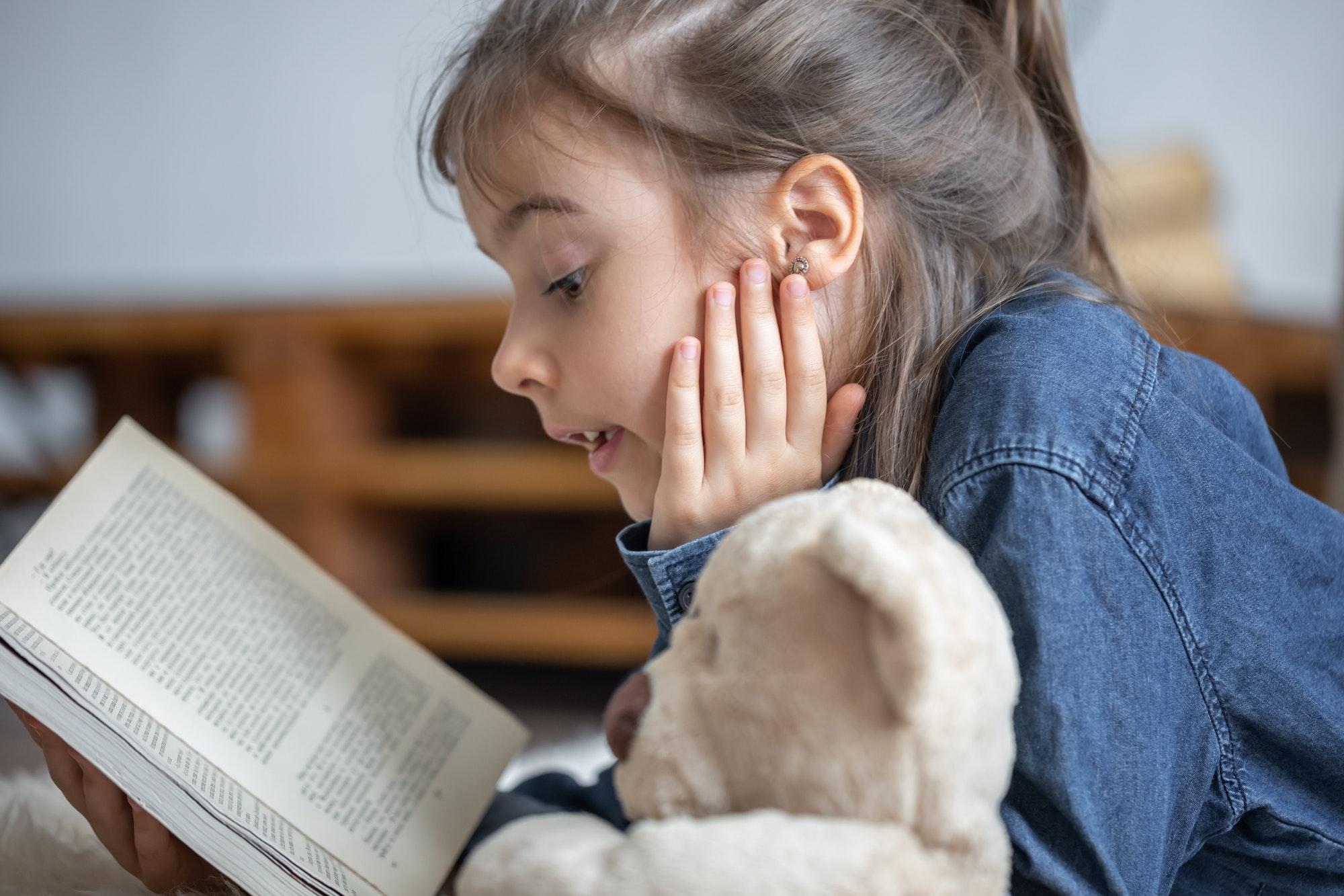 Little girl reads a book with a teddy bear.