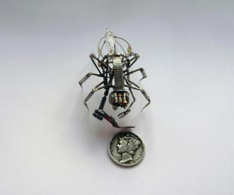 Spider made from watch parts next to coin to demonstrate small size
