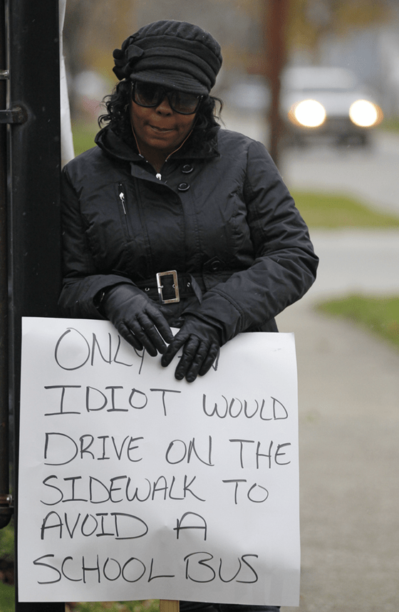 """Woman holding """"idiot"""" sign"""