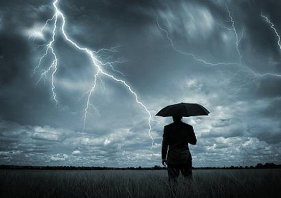 Man watching a thunderstorm full of lightning