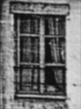 A child peering out of the window of the white building