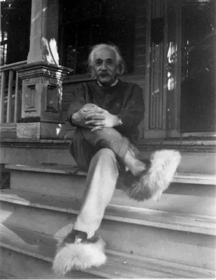 Albert Einstein sitting on the steps of his home wearing fuzzy slippers.