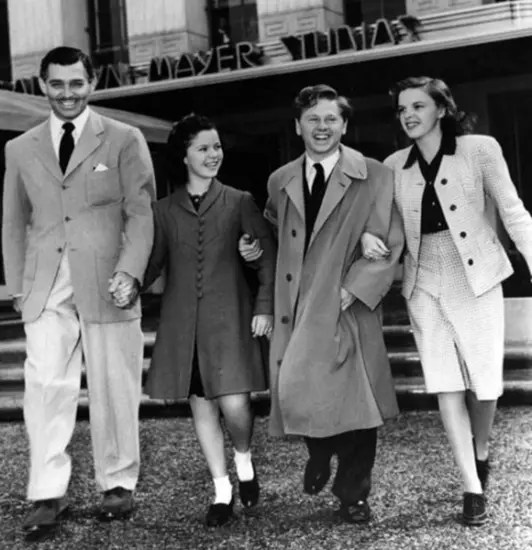 Clark Gable, Shirley Temple, Mickey Rooney, and Judy Garland skipping out of a movie studio.