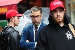 Galvin McInnes flanked by two Proud Boys members wearing red MAGA hats