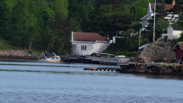 UNDER VANN: Båten ligger halvt nedsunket ved en brygge i Saltrødbukta. Bildet er tatt fra Sandstø brygge. Foto: Esben Holm Eskelund