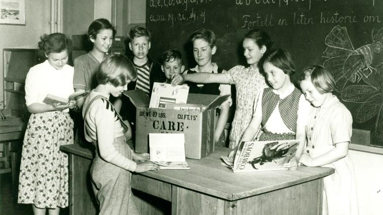 CARE-PAKKE: Elever ved Ruseløkka barneskole i Oslo viser glede over å motta amerikanske barnebøker. Etter krigens slutt bredte studier i engelsk om seg i hele Norge, men finansiering av innkjøp av bøker var et stort problem på grunn av den økonomiske situasjonen i Norge. Foto: Care