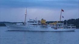 KONGESKIPET: Kongeflagget vaiet om bord på KS Norge på vei inn Tromøysund lørdag kveld. Det fikk fart på spekulasjonene om at Kong Harald V er om bord. Foto: Margrethe Andersen Havegaard