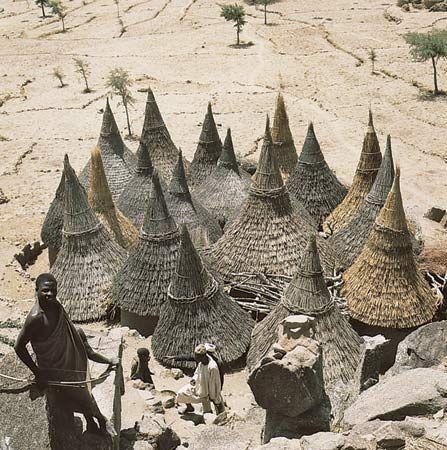 Telhados cônicos de casas cilíndricas em um composto Matakam, Camarões cobertas de palha. por Rene Gardi