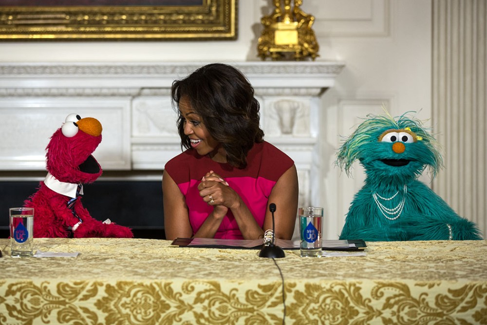 "First Lady Michelle Obama, with Sesame Street Muppets Elmo and Rosita, makes a ""Let's Move!"" announcement about marketing healthier foods to children, in the State Dining Room of the White House, Oct. 20, 2013. (Official White House Photo by Lawrence Jackson)"