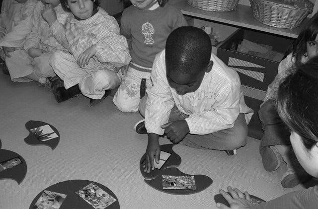 Criança negra montando um jogo na escola