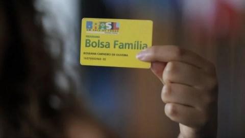 Mão de umaa mulher segurando o cartão do Bolsa Familia