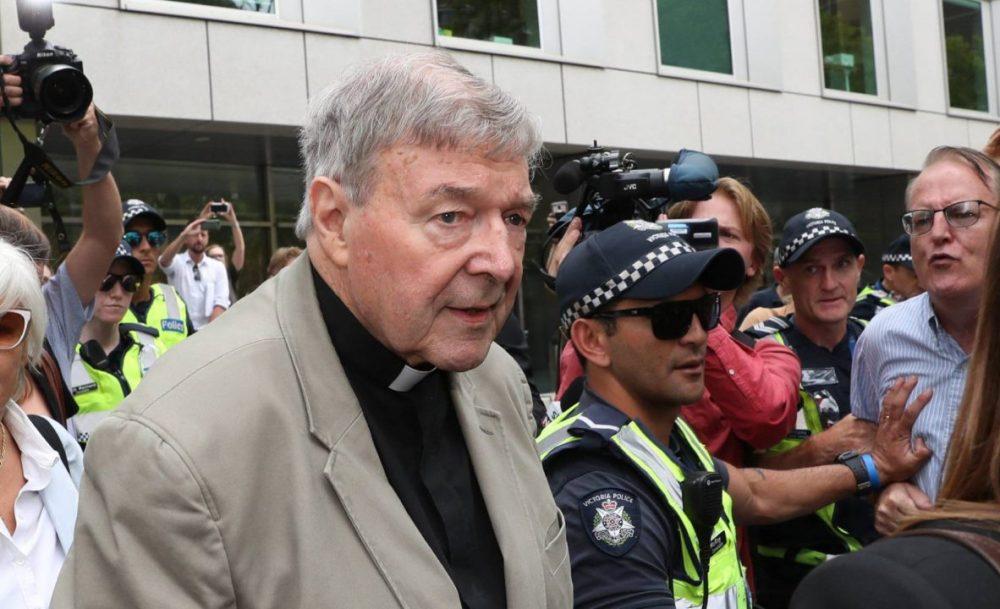 Homem idoso,branco, com cabelos grisalhos em ambiente aberto com iluminação natural do dia, diante de jornalisas e sendo protegido por políciais. O senhor aparenta ter mais de 70 ano, veste túnica de padre preta e um casaco beje