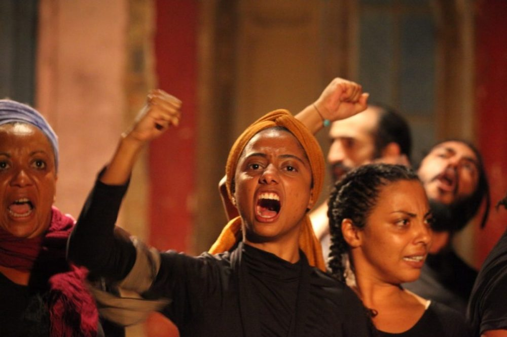 Grupo de atrizes gritando em cena da peça Esperança na Revolta