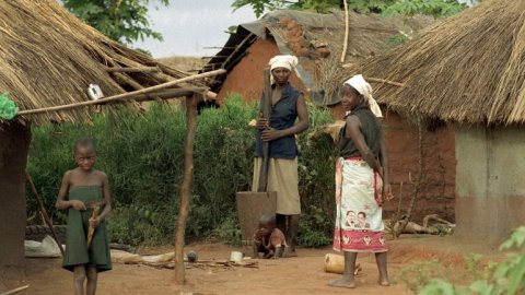 Duas mulheres guineenses e uma criança aproximadamente de 9 anos em frente a casas de sapé. Uma mulher com um pau e um pilão e outra com braços para trás e olhando para o fotográfo