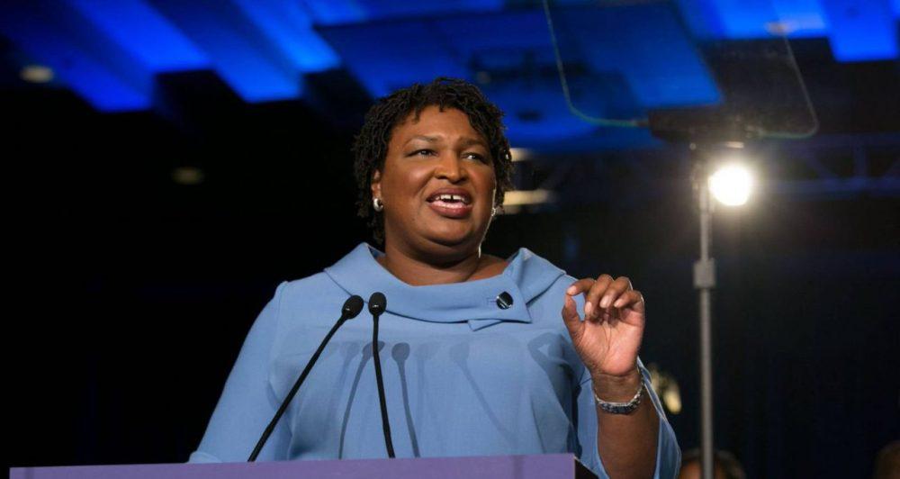 Stacey Abrams de vestido azul discursando ao microfone