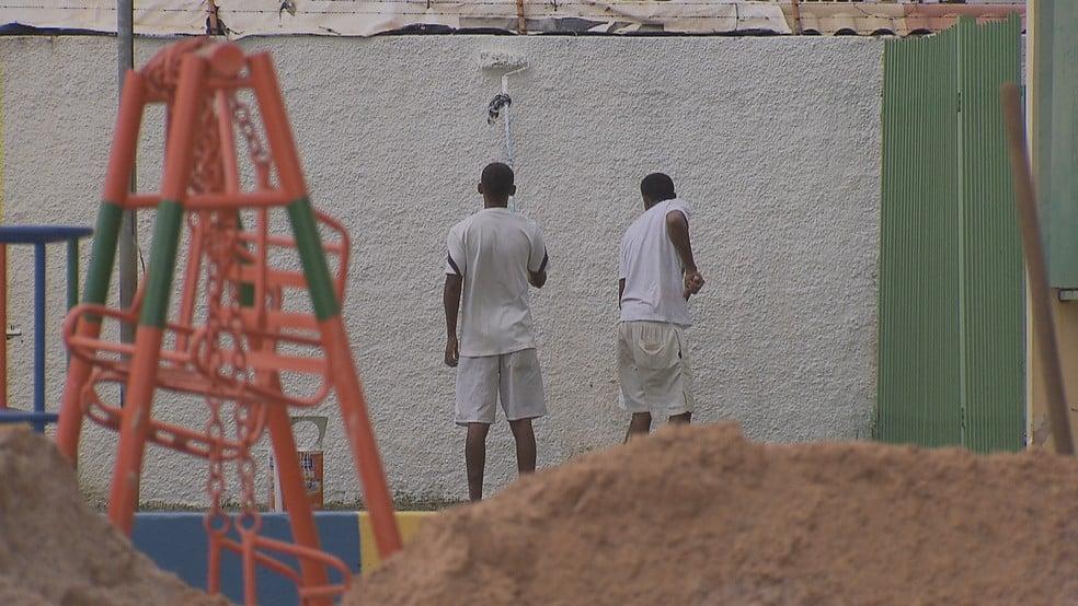 Homens pintam muro do CED 1 na Estrutural após convênio de gestão compartilhada entre secretarias de Educação e Segurança