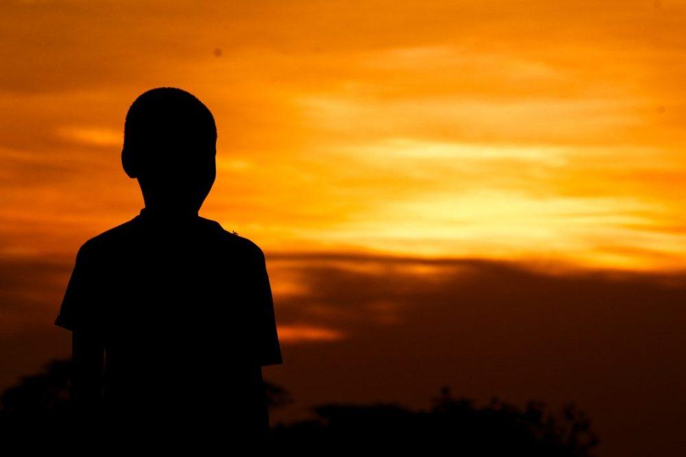 Uma criança sozinha olhando para o horizonte (Foto: @ ARTSY SOLOMON)