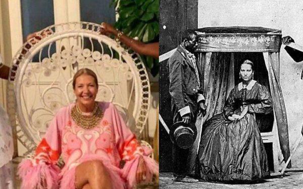 """Donata Meirelles, diretora da revista Vogue, evoca e faz reviver as """"cadeirinhas de carregar"""" do século XIX, com dois escravos ao lado de uma figura branca ao centro"""
