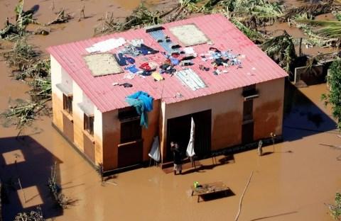 Homem acena perto da sua casa inundada após a passagem do Ciclone Idai no distrito de Buzi, perto de Beira, em Moçambique