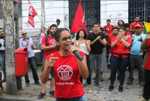 """Deputada JÔ Cavalcante, mulher negra de cabelo liso e preso, em pé discusando. Com camiseta escrita """"A luta é pra valer""""."""