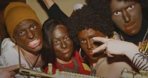 Quatro pessoas brancas, realizando Blackface, pousando para uma foto.