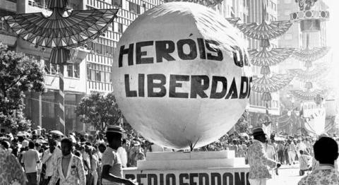 """Imagem em preto e branco que mostra um balão escrito """"Heróis da Liberdade)"""
