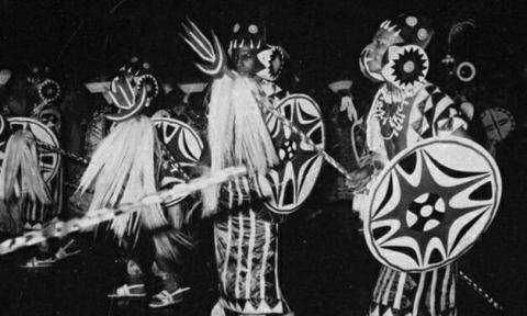 Imagem em preto e branco, onde homens negros aparecem caracterizados interpretando em sua ala.